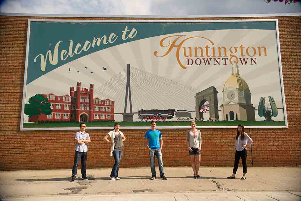 Students stand in front of Welcome to Huntington sign