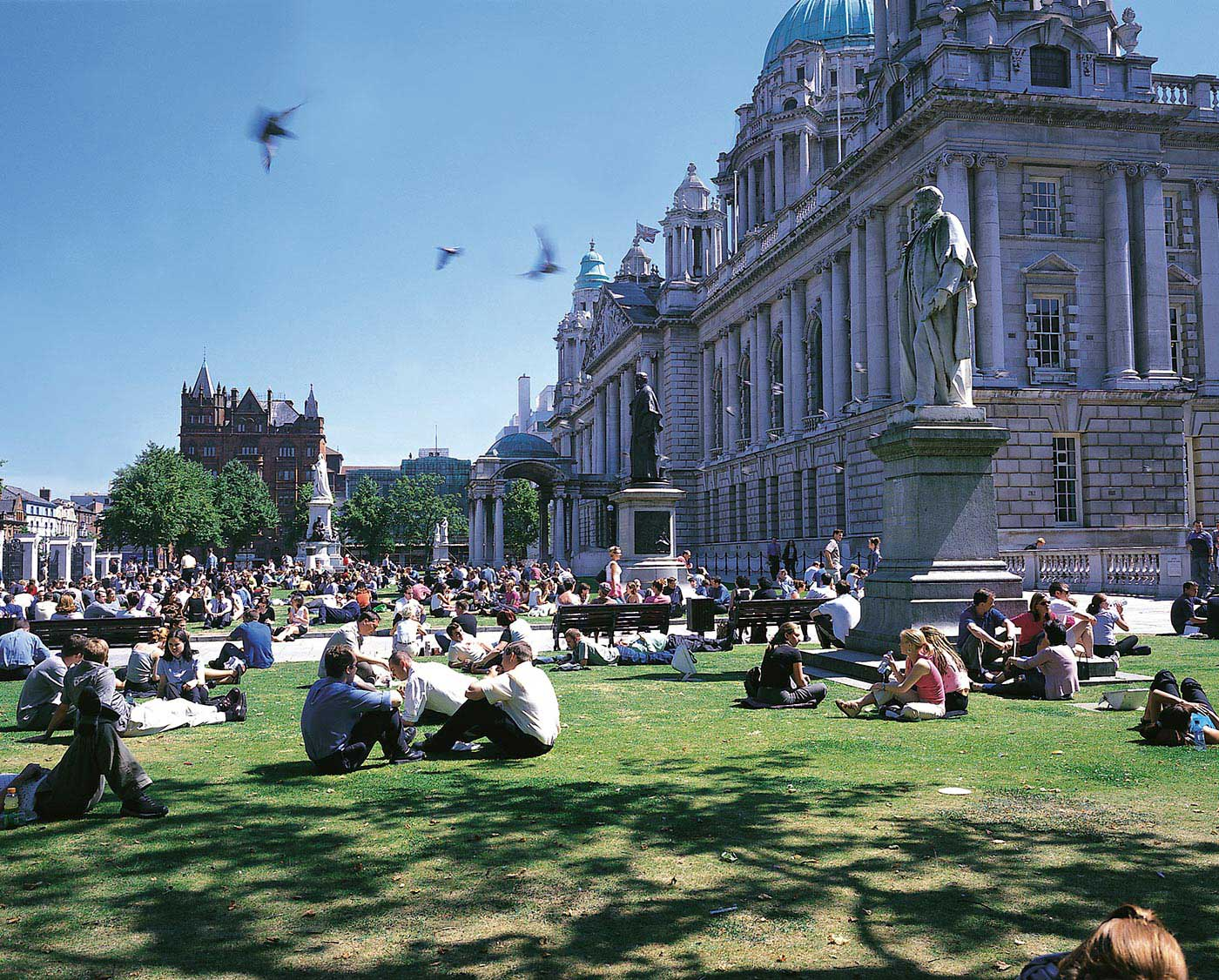 People sitting on the grass outside Belfast City Hall