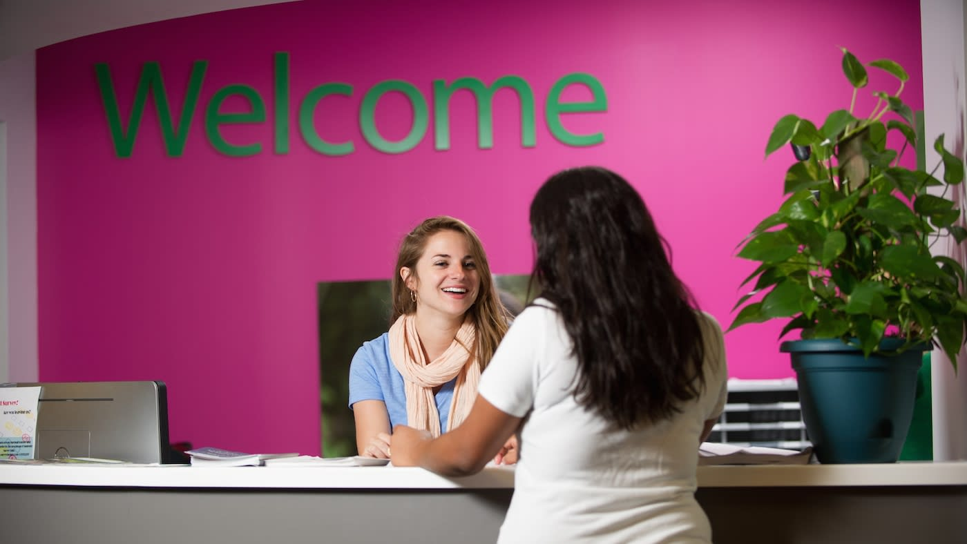 INTO staff smiling at the reception desk